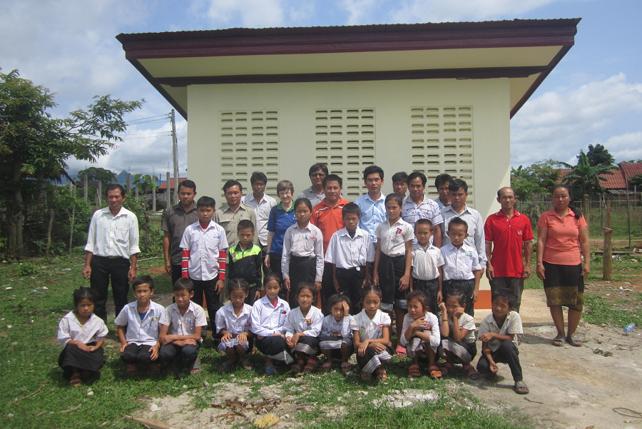 Students and community members in front of the toilet block they built as part of a Child Aid project