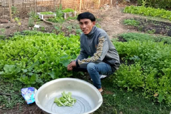 Mr Vieng Sihalat, 29 years, in his home garden